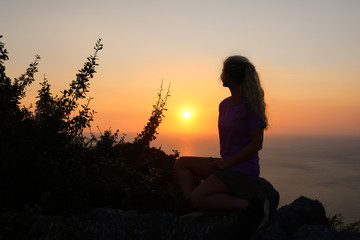 Happy woman enjoying on the top of the mountain at sunset.