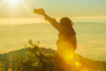 young asian woman taking photo with smart phone at top of mountain and mist
