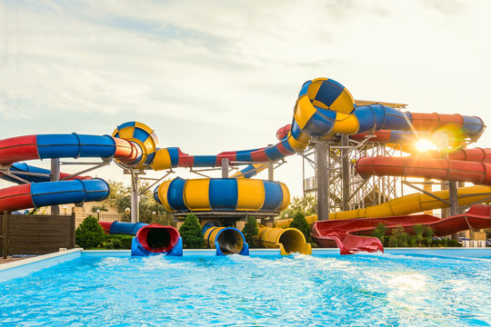 Long spiral water slides in the outdoors seasonal water park at evening sun