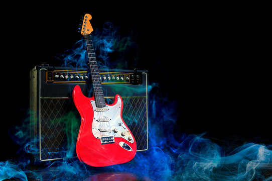Red electric guitar and amplifier surrounded by blue smoke on dark empty stage. Copy space for text.
