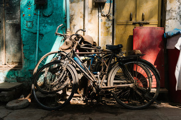 Old broken bicycles left outside of the house