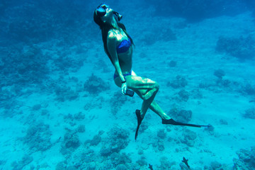 Young woman snorkeling with camera take photo over coral reef in blue sea