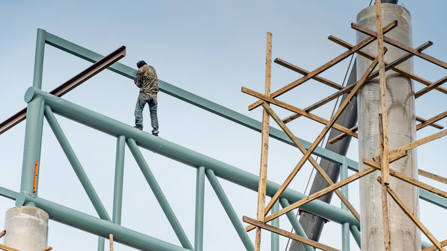 Male construction worker standing on steel truss structure at construction site. Wide span building construction process.