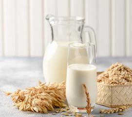 The concept of a vegetarian diet. Oat milk in the glass with jug of oat milk and oat and oat ears.