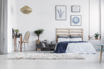 Wicker chandelier under the ceiling of bright scandinavian bedroom interior with king size bed and fashionable grey nightstand