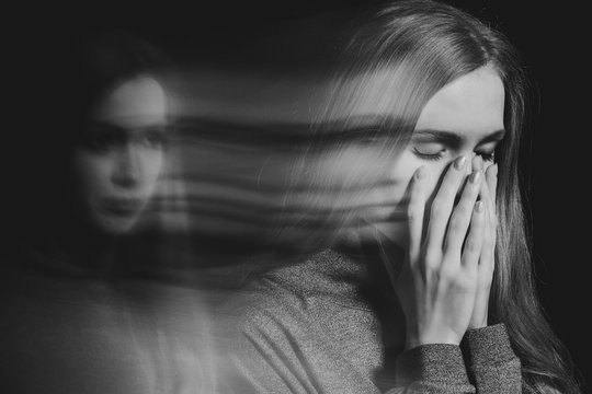 Blurred black and white picture of young beautiful redhead girl with obsessive compulsive disorder covering her mouth and closing her eyes
