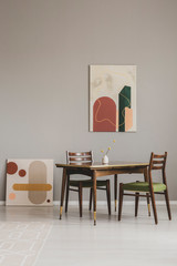 Abstract paintings on grey wall of retro dining room interior