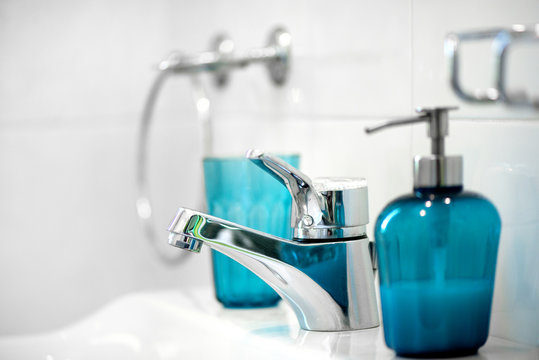 Modern tiled bathroom sink basin faucet paired with blue or turquoise glass soap containers. Concept of cleaning the bathroom.