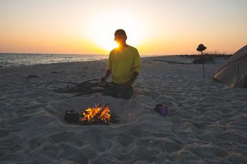 Adventurer sits next to burning bonfire on the beach