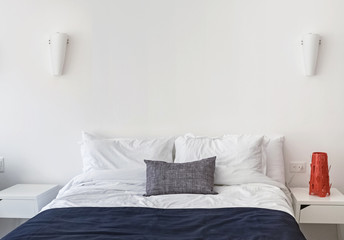 Modern light minimalist bedroom with white bedsheets.