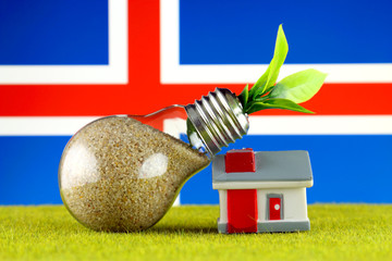 Plant growing inside the light bulb, miniature house on the grass and Iceland Flag. Renewable energy. Electricity prices, energy saving in the household.