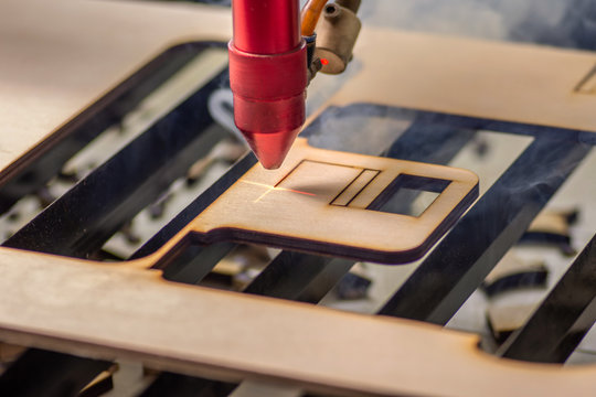 Laser engraver working and engraving wooden board