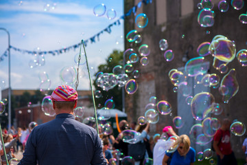 A freelance clown blowing hundreds of tiny, small and big bubbles at outdoor festival in city center. Concept of entertainment, birthdays. Kids having fun. Shower of bubbles flying in the happy crowd