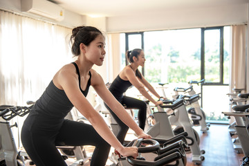 Attractive woman  biking in gym, exercising legs doing cardio workout cycling bikes - Image