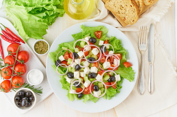 Greek salad on white plate on old rustic white wooden table, fresh salad with tomatoes, cucumbers, feta, onion. Top view