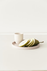 A cut conference pear on a plate on a white table.