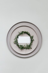 A small rosemary wreath on a decorated tabletop with a taupe plates and an empty place card.