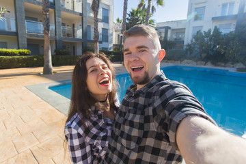 Travel, vacation and holiday concept - Happy couple having fun taking selfie near a swimming pool