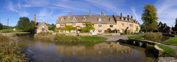 Stitched panorama of the idyllic Cotswold cottages in early autumn by the little River Eye in Lower Slaughter, Gloucestershire, UK