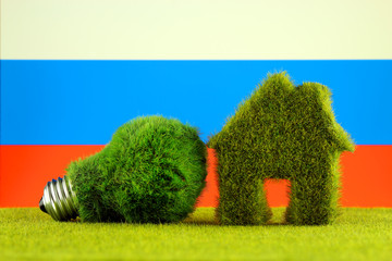 Green eco light bulb, eco house icon and Russia Flag. Renewable energy. Electricity prices, energy saving in the household.