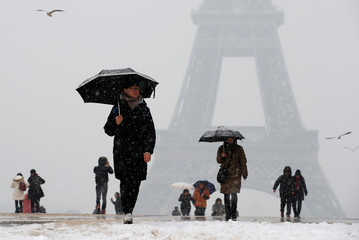 People use umbrellas against the snow as they walk across from the Eiffel Tower in Paris