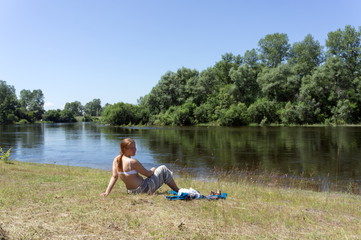 Red-haired girl sits on the bank of the river against a background of trees, in a summer sunny day.