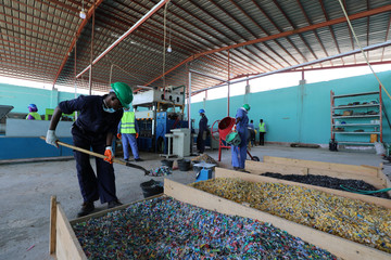 Man shovels shredded plastic litter to be recycled into roofing tiles in Mogadishu