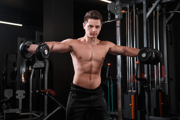 Athletic man raises dumbbells to the sides in the gym.