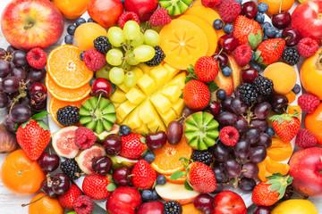 Wall Mural - Healthy fruit platter background, strawberries raspberries oranges plums apples kiwis grapes blueberries mango persimmon, top view, selective focus