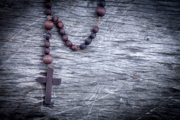 Close up rosary against wooden background as symbol of salvation and eternal life.
