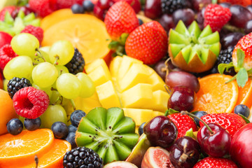 Healthy fruit background filled with strawberries raspberries oranges plums apples kiwis grapes blueberries mango persimmon pineapple, selective focus