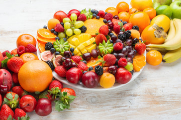 Wall Mural - Healthy platter with colorful rainbow fruits, strawberries raspberries oranges plums apples kiwis grapes blueberries mango persimmon, copy space, selective focus