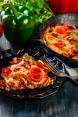 Portion of frittata with eggs, sausage chorizo, red pepper, green pepper, tomatoes, cheese and chili in a plate on wooden table.