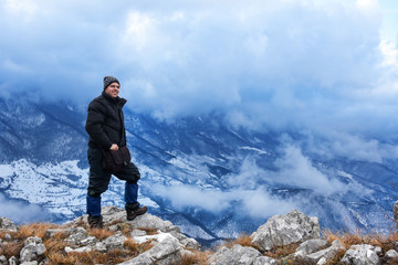 Hiker standing on a mountain top and looking into dynamic sky. Foggy mountain, Colorful winter landscape