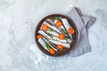 Sardines or baltic herring with parsley and tomatoes slices on ceramic plate