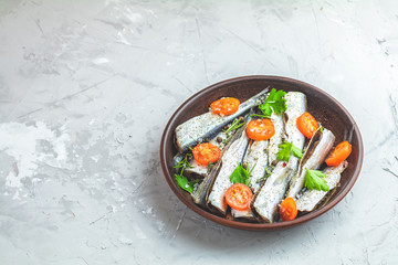 Sardines or baltic herring with rosemary, thyme, parsley,  tomatoes slices and spaces