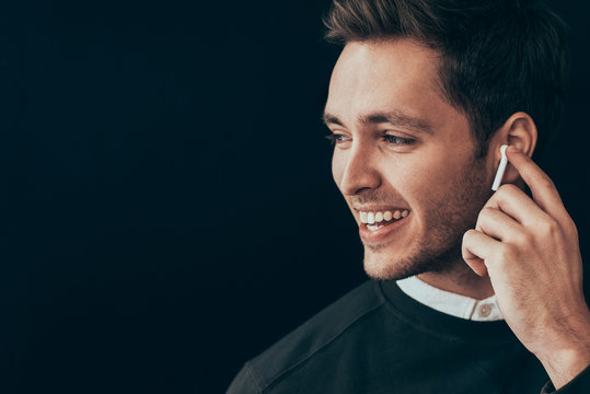 Closeup horizontal portrait of young handsome man smiling and have a call with a colleague isolated on black background holding wireless earphone with finger. Businessman using wireless headphone.