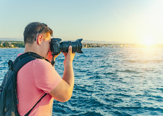 Man with a camera photographing the sunset on the sea coast.