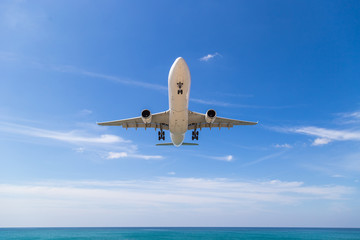 A passenger plane taking off in the cloudy sky. Aircraft flies over the sea and the tropical island.