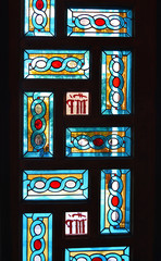 interior scene of a greek Orthodox church with colorful stained glasses on the door