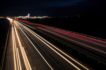 Motion blurred light tracks glowing to the darkness of highway traffic to the city just after sunset. Creative long time exposure photography.