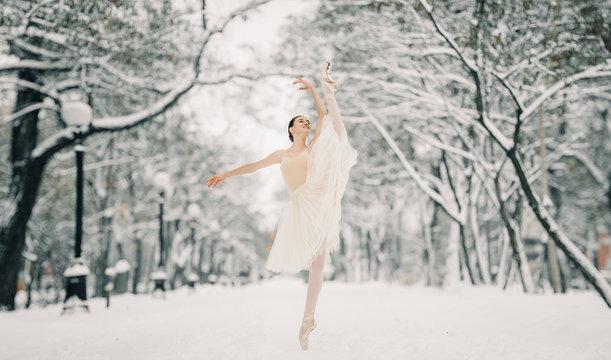 Beautiful ballerina is dancing at walkway of snowy city