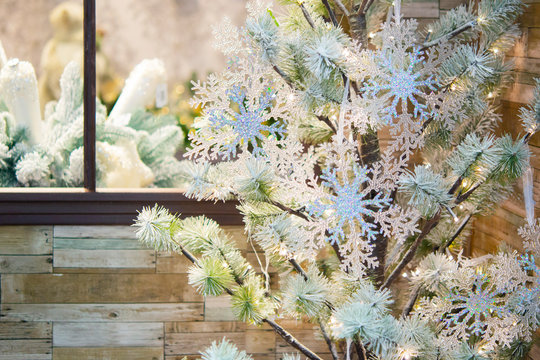 Decorative snow-covered fir-tree decorated with decorative large shiny snowflakes at the window close-up. Christmas Winter New Year Scenery background. Concept