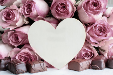 Beautiful retro soft pink rose flower background with wooden heart and room for text surrounded by chocolate candy..