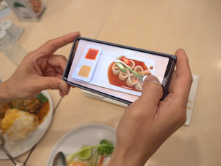 Happy time of young man using smart phone taking photo which take a picture food before eating in the resturant, photography on table background