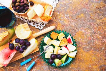 Still life of cheese, fruit, wine on a natural marble surface