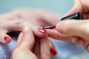 Closeup of manicurist applying nail polish