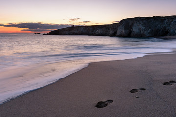 French landscape - Bretagne. A beautiful beach with footprints and wild cliffs in the background at sunset.