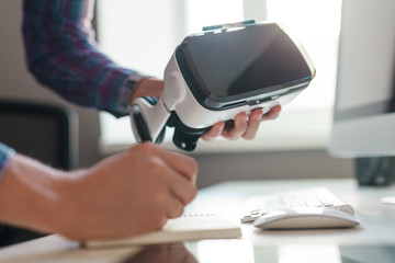 Crop hands with VR goggles making notes