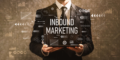 Inbound marketing with businessman holding a tablet computer on a dark vintage background